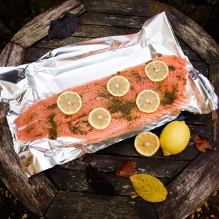 A side of salmon baked with herbs and lemon, perfect to feed a crowd.