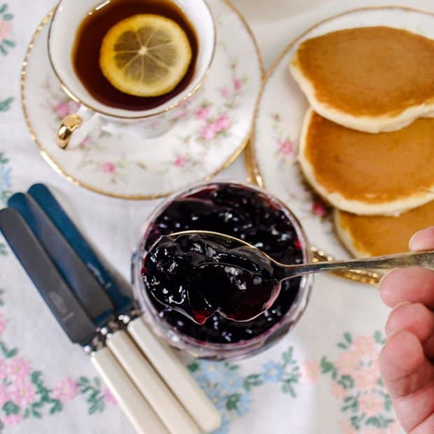 Blackberry and Apple Jelly on a spoon with pancakes and a cup of tea