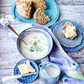 Bowl of Cullen Skink with spoon in it, soda bread, butter and jug of cream.