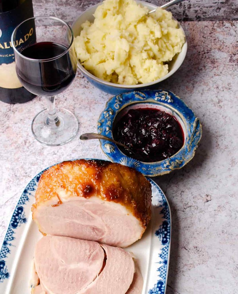Cooked Ham with mashed potatoes in bowl, Cranberry & Red Wine Sauce in bowl, glass of wine and bottle.